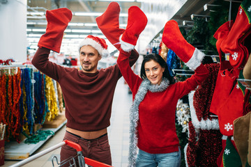 Happy couple choosing christmas socks for gifts