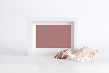 White empty photo frame with pink color inside and sea shells, on white background. Clipping path inside the frame