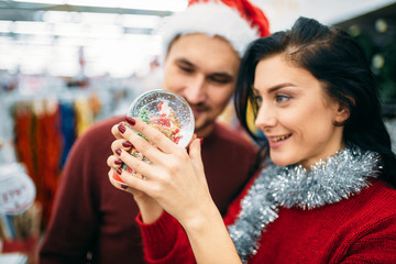 Couple looks on snow globe in supermarket