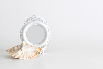 White round vintage photo frame with light grey color inside and a big sea shell, empty space for your text on the left, on white background. Clipping path inside the frame