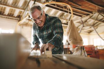 Smiling mature man working in carpentry workshop Wall mural