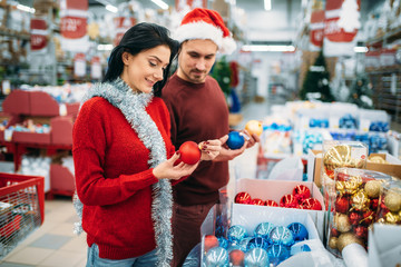Couple chooses christmas tree balls in supermarket