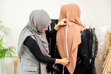 Female muslim designer measuring back of customer