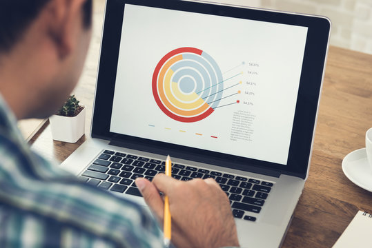 Man analyzing business chart in laptop