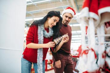 Couple chooses christmas souvenir in supermarket