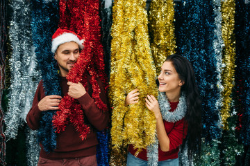 Young couple plays with holiday fluffy garland