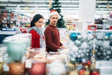 Couple buying Christmas souvenirs in supermarket