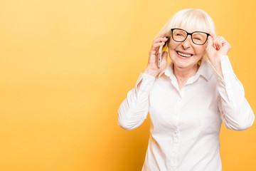 Phone conversation. Positive aged woman smiling while talking on the phone isolated over yellow background.