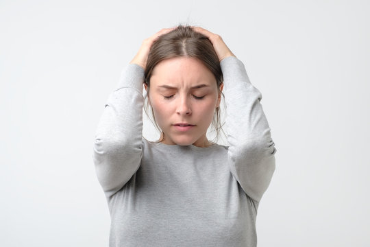 Young stressed woman holding head in hands