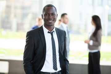 handsome african businessman with group of businesspeople on background.