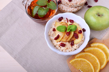 Porridge with caramelized apples and dried cranberries topped with mint surrounded by breakfast ingredients
