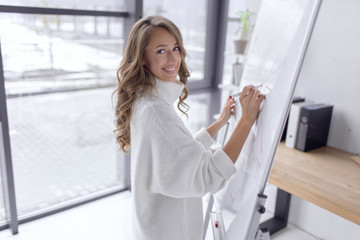 Business girl holds a conference and writes gafi on the board