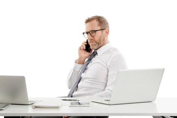Businessman making call and working on laptop