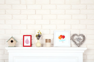 White fireplace with photo frames, nesting box and flowers in vase