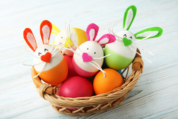 Eggs with funny rabbit faces in basket on wooden table