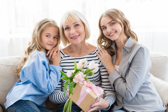 Women generation. Granny with presents, mom and daughter hugging grandmother