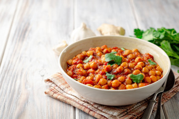 Spicy Chickpea curry Chana Masala in bowl on wooden table. Traditional Indian dish. Selective focus.