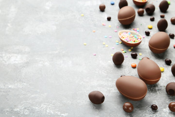 Chocolate easter eggs with colorful candies on grey wooden table
