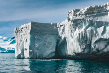 Keuken foto achterwand Antarctica Close-up sunlit iceberg. Antarctica scene in blue and white tints. Amazing snow covered block of ice with icicles floating among the polar ocean. The cloudy sky background. Picturesque winter scenery.