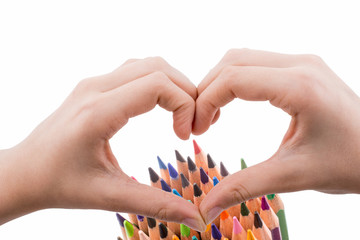 Color pencils of various color behind a heart shaped hand