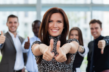 business concept - attractive businesswoman with team in office showing thumbs up.