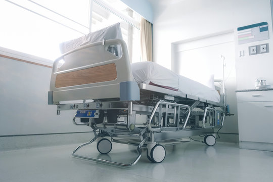 Empty hospital bed in hospital ward