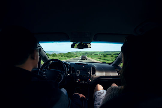 Couple in love enjoying travel. Beautiful young smiling couple sitting on front passenger seats and driving on country road on trip. Rear passenger POV. View from the back. Exciting journey concept.