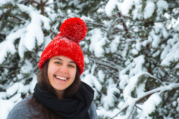 portrait of young smiling woman in winter clothes in red hat with bubo fir tree in background