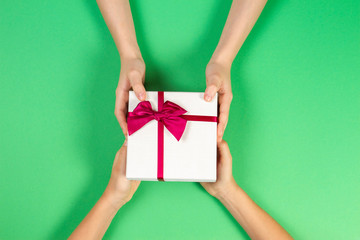 Congratulations background. Top view of two persons hands giving and receiving a present gift box with ribbon on green background. Top view. Present for birthday, valentine day, Christmas, New Year.