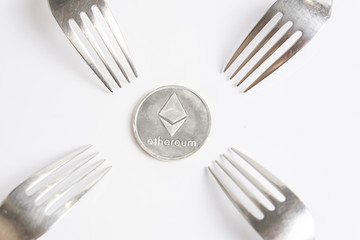 Ethereum cryptocurreny silver coin placed between forks on white background, hard fork