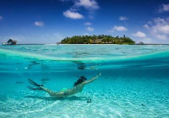 Sommerurlaubs Konzept : Frau im Bikini taucht in klaren, exotischen Gewässern vor einer tropischen Insel; Splitaufnahme