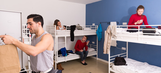 Man putting belongings in locker in hostel