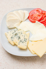 Assorted cheese sliced cheese with tomato on white plate
