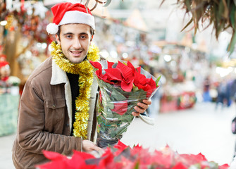 Joyful young man in Christmas hat  looking flowers and Christmas toys at fair