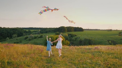 732ee552 0:11 A young woman with her daughter launches two kites, runs fun, and  enjoys active