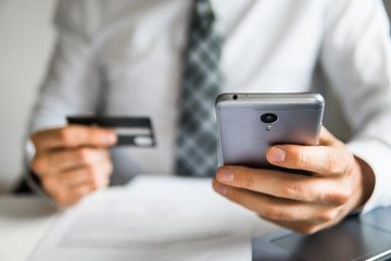 Online trading on the currency exchange. Payment of goods online. Online payments through the phone. Smartphone and Internet Commerce. Young businessman with a bank credit card in his hands.