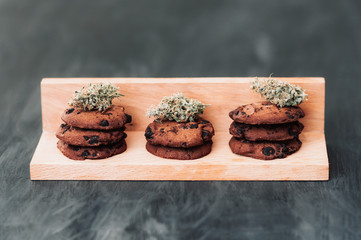 Chocolate cookies with marijuana. Sweets with cannabis. Cannabis buds on a black background. Baking with the addition of CBD. Sweets with weed. Copy-space