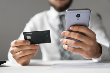 Smartphone and Internet Commerce. Payment of goods online. Young businessman with a bank credit card in his hands. Online payments through the phone. Online trading on the currency exchange.