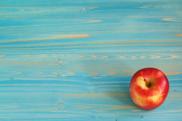 A ripe red Apple on a blue table. Background for the inscription