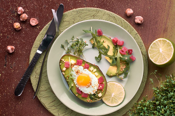 Keto diet dish: baked Avocado boat with ham cubes, quail egg and cheese served with green rucola salad