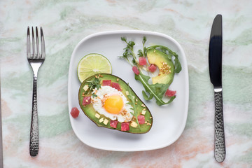 Baked Avocado boat with ham cubes, quail egg and cheese served with green rucola salad