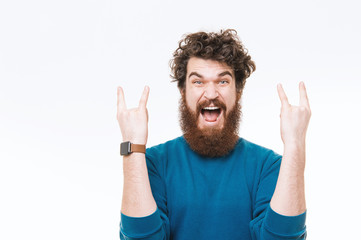Hipster guy  in blue sweater, rock gesture standing over white background