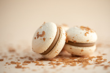 Creamy macarons close-up on beige background