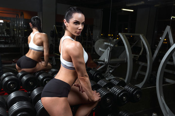 Pretty young brunette girl is relaxing on dumbbells in the gym