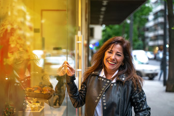 A smiling mature woman in a leather jacket checking the storefront at night.