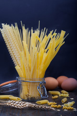 Different types of pasta, macaroni and spaghetti. Italian pasta in a glass jar on a wooden background