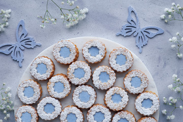 Top view of flower Linzer cookies with blue glazing on light background decorated with white flowers