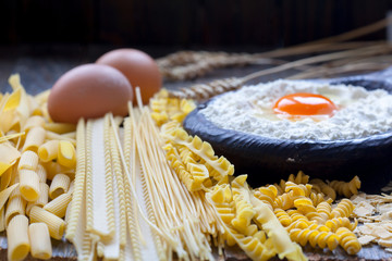 Different types of whole wheat pasta and spaghetti. Flour and egg yolk in wooden bowl.