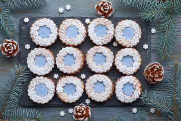 Top view of flower Linzer cookies with blue glazing on rustic winter background