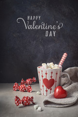 Hot chocolate with marshmallows,white cup with heart on the table, greeting text
